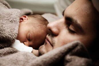 newborn baby sleeping on father's chest